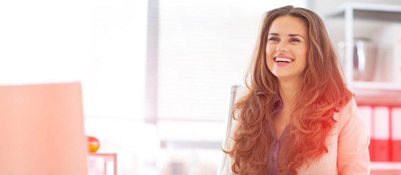 Lächelnde Frau am Schreibtisch